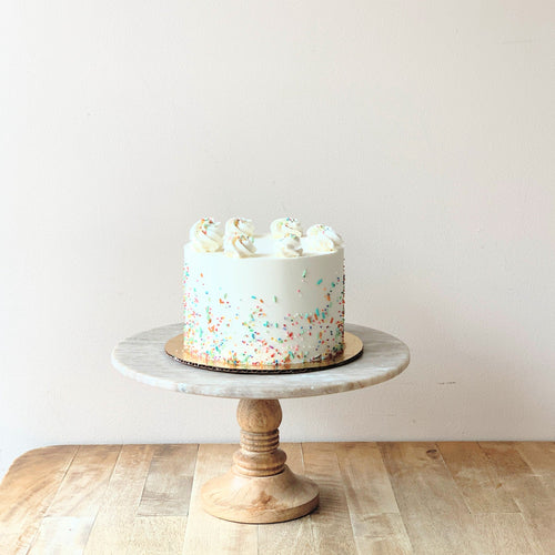 An image of a white buttercream frosting cake decorated with piped rosettes of buttercream on top and colorful sprinkles on the sides. The cake sits atop a marbled cake stand with a wooden base.