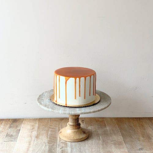 Picture of a white cake with golden brown caramel covering the top of the cake and dripping down the sides. Cake is set atop a wooden and marble cake pedestal.