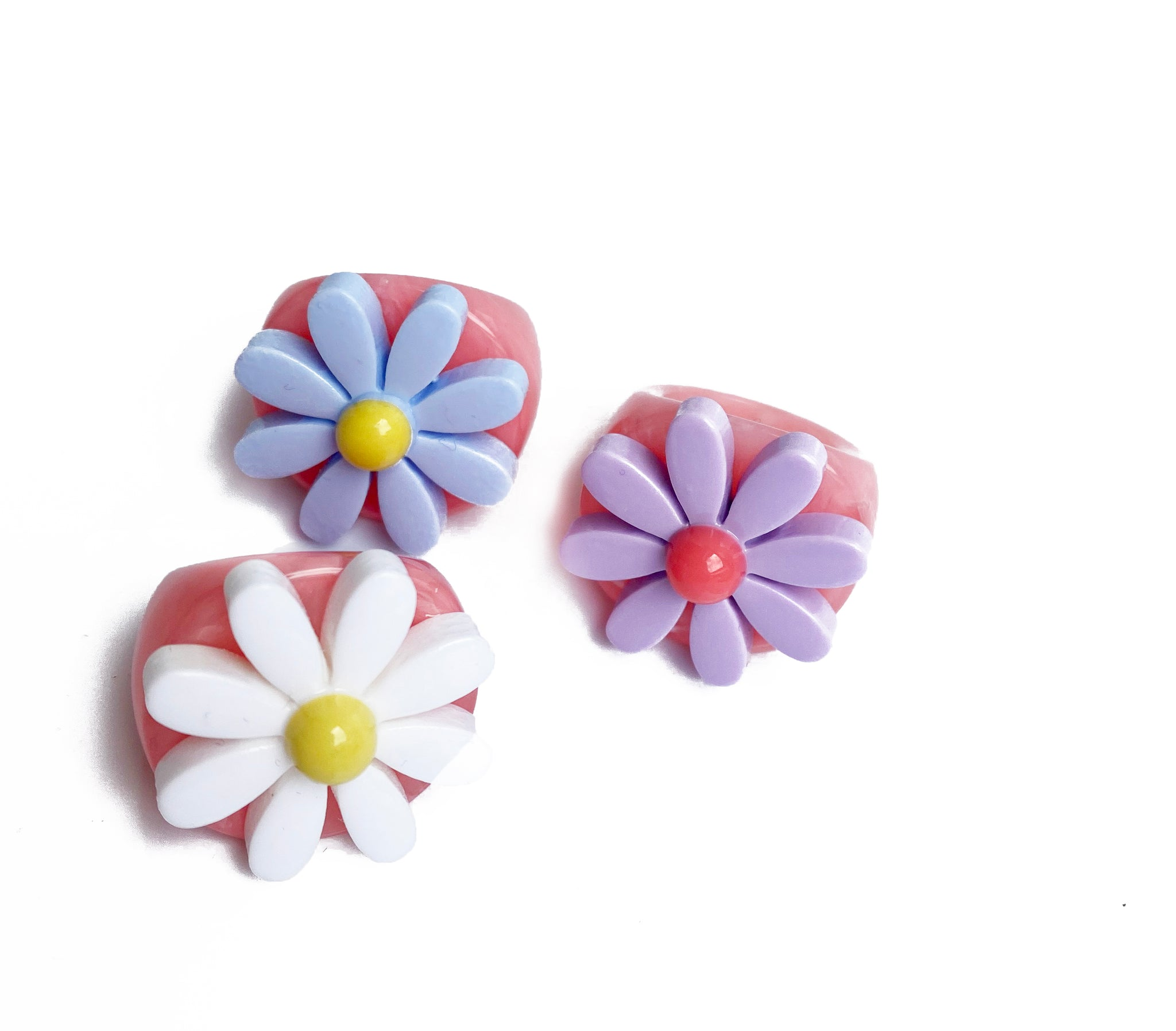 3 resin bubble rings with pink bases and flowers on the front. One is white with a yellow base, one is purple with a pink base and the third is blue with a yellow base.