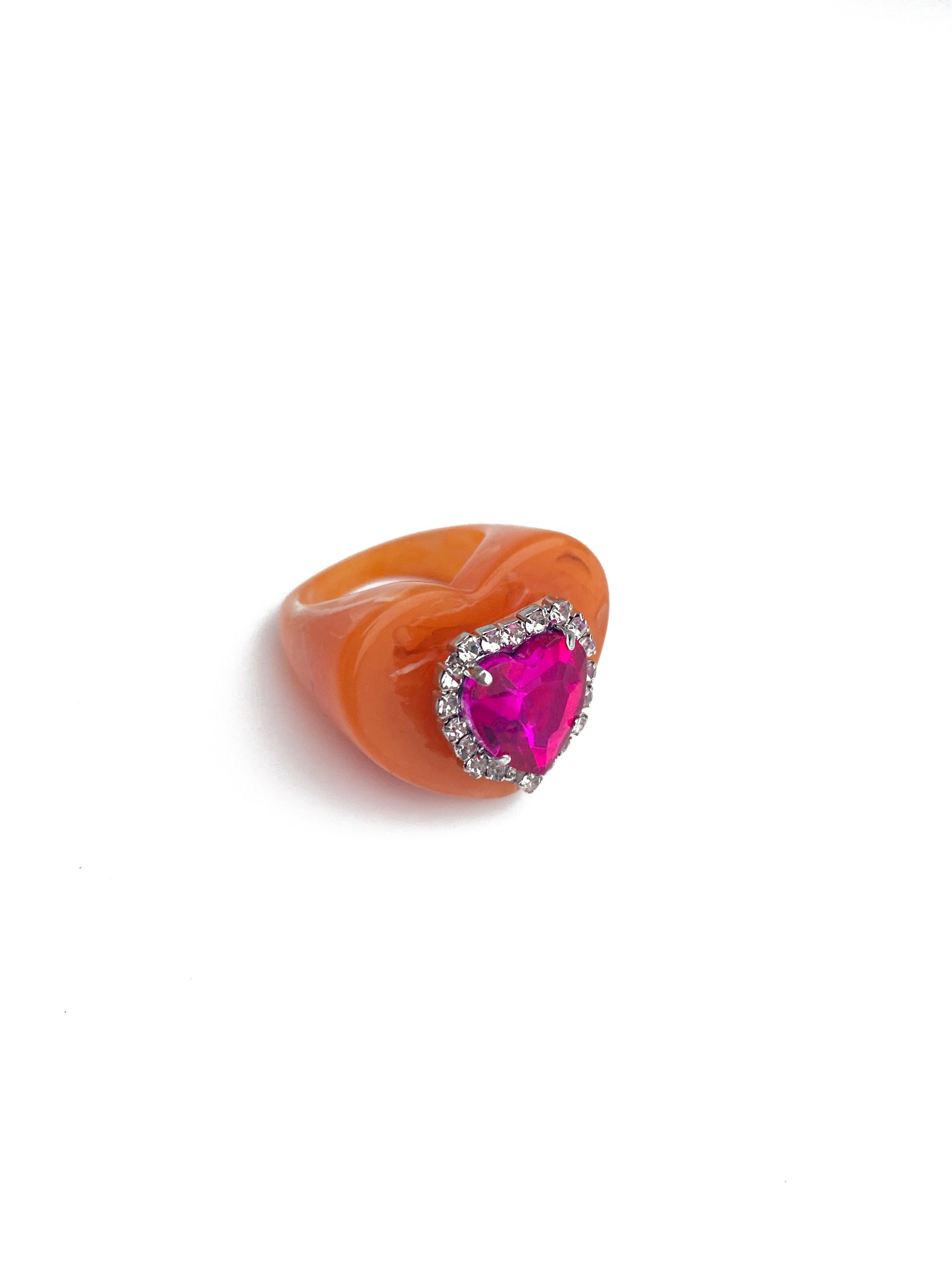 Orange heart-shaped resin ring with heart-shaped pink faux diamond gem in centre and clear diamante gems all around the centre gem.