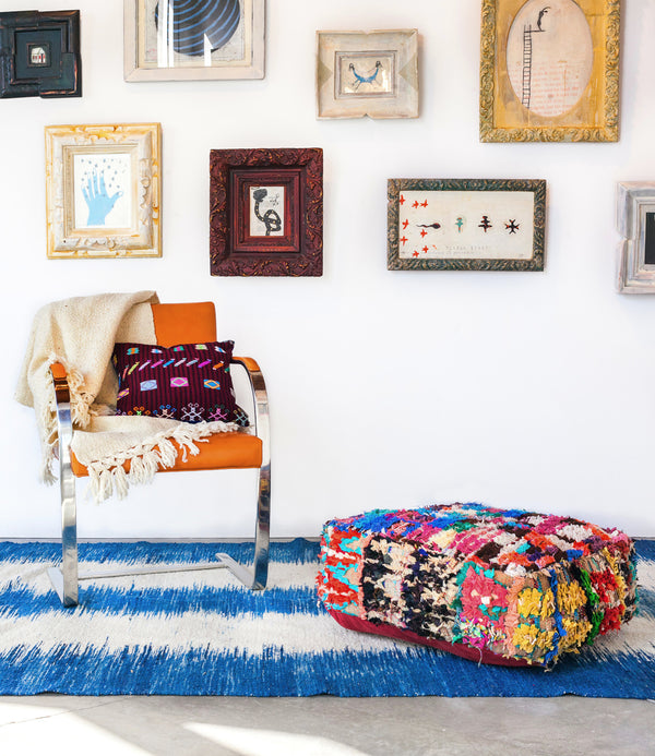 Indigo Rug in a styled room with chair and pouf.