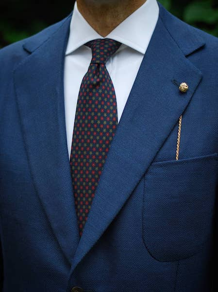 Navy jacket and lapel pin