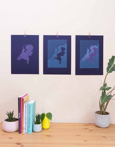 Triptych of Navy letterpress map 'Below the Sea' showing 2 layers of coloured print next to final print on wall.