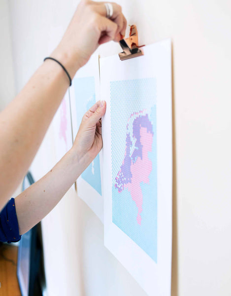 Hand clipping Letterpress patterned map of The Netherlands to wall. Magenta and blue patterned kaba ornaments.