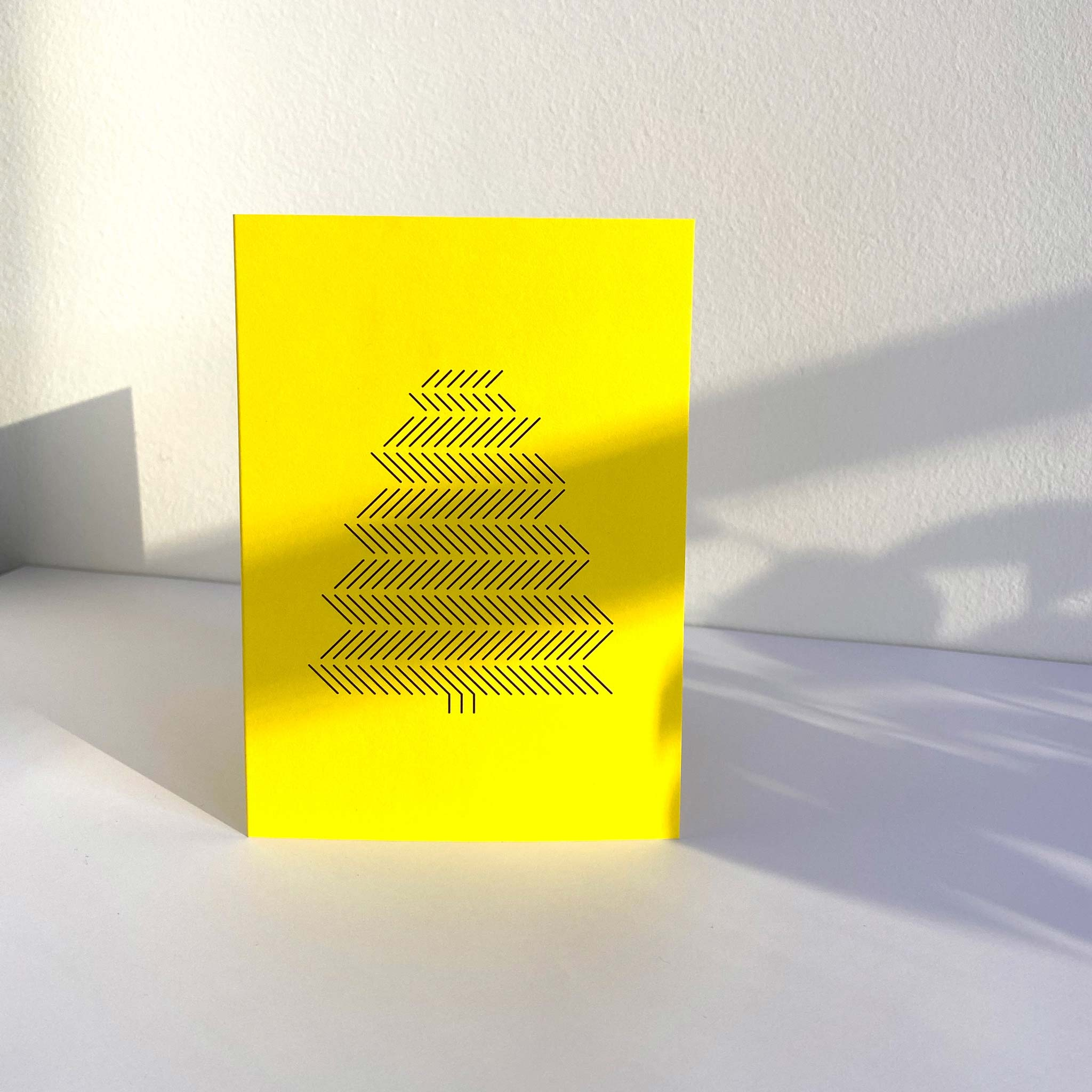 Standing yellow A6 christmas greeting card with black graphic print of pine tree