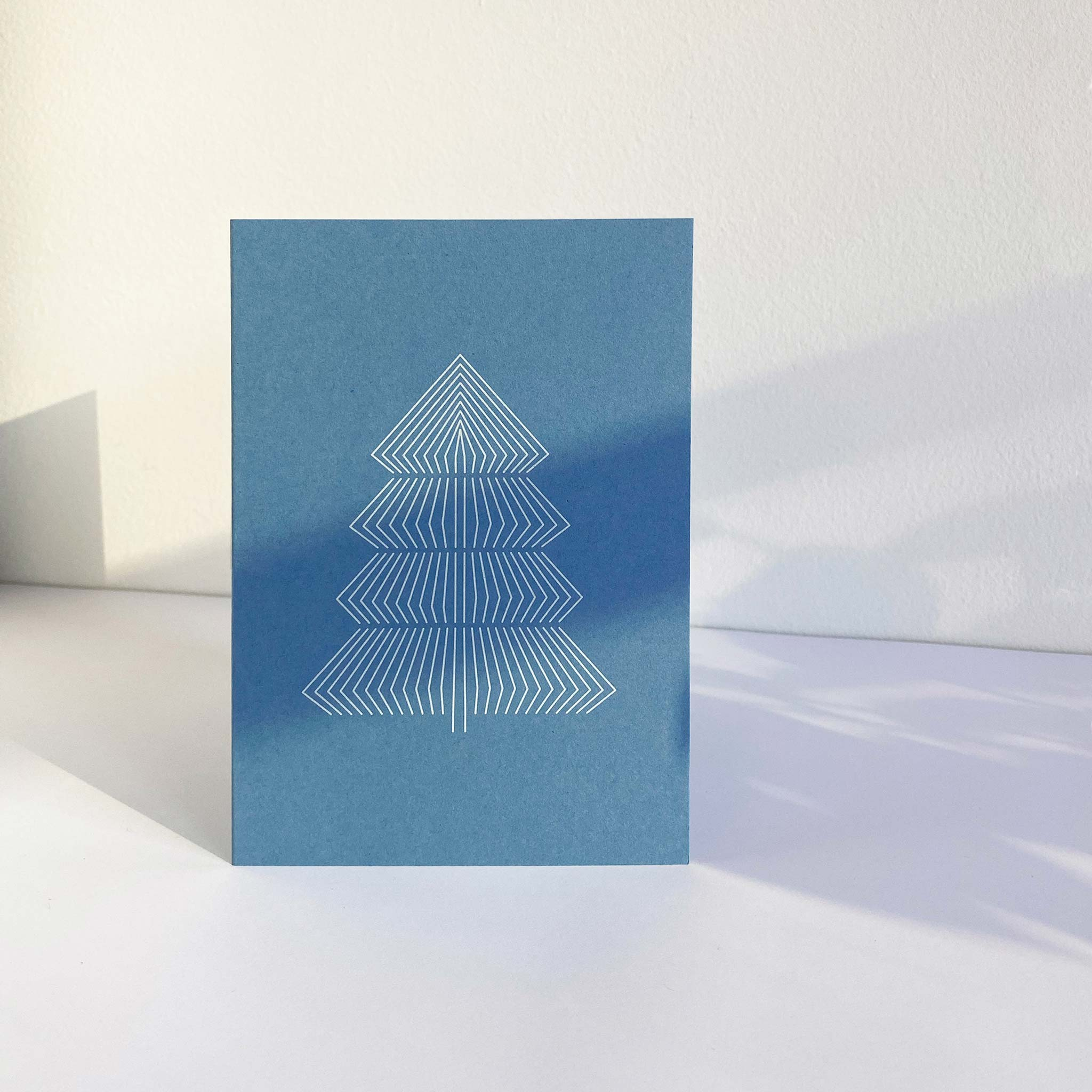 Standing sky blue A6 christmas greeting card with graphic print of fir tree