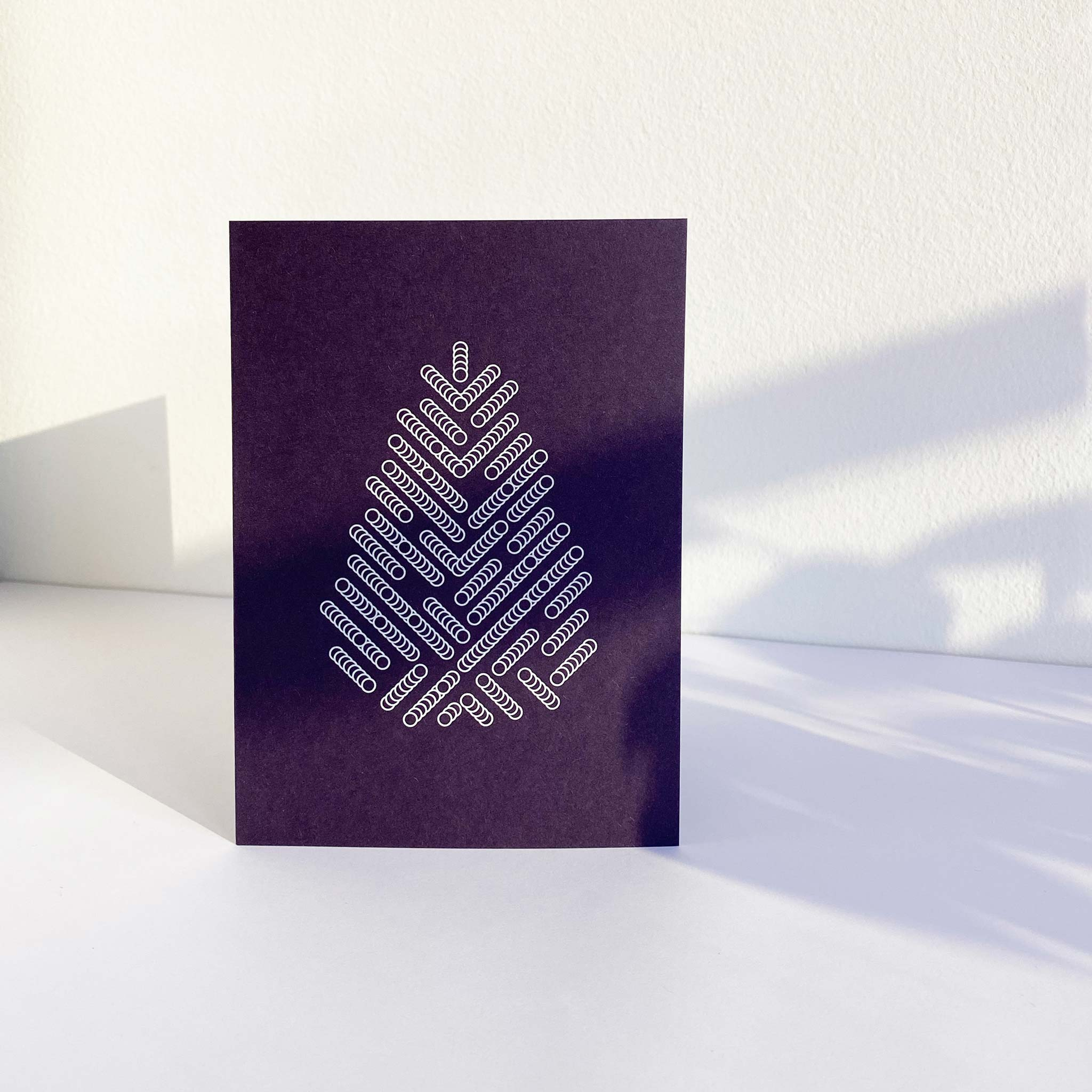 Standing deep purple A6 christmas greeting card printed with white graphic print of spruce tree.
