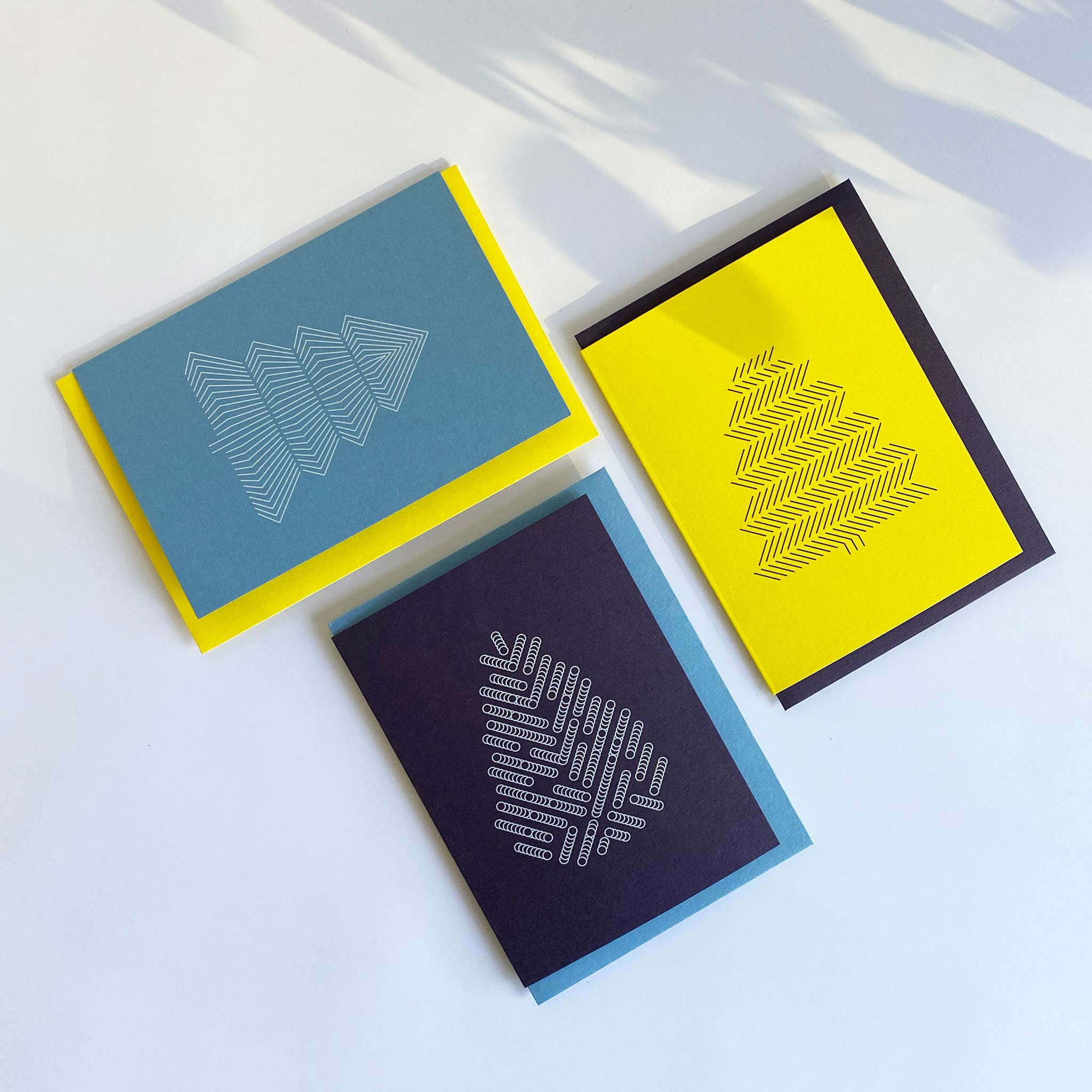 Flat lay of three christmas greeting cards with geometric tree prints. Deep purple with white tree, sky blue with white tree and bright yellow with black tree. Alternating coloured envelopes.