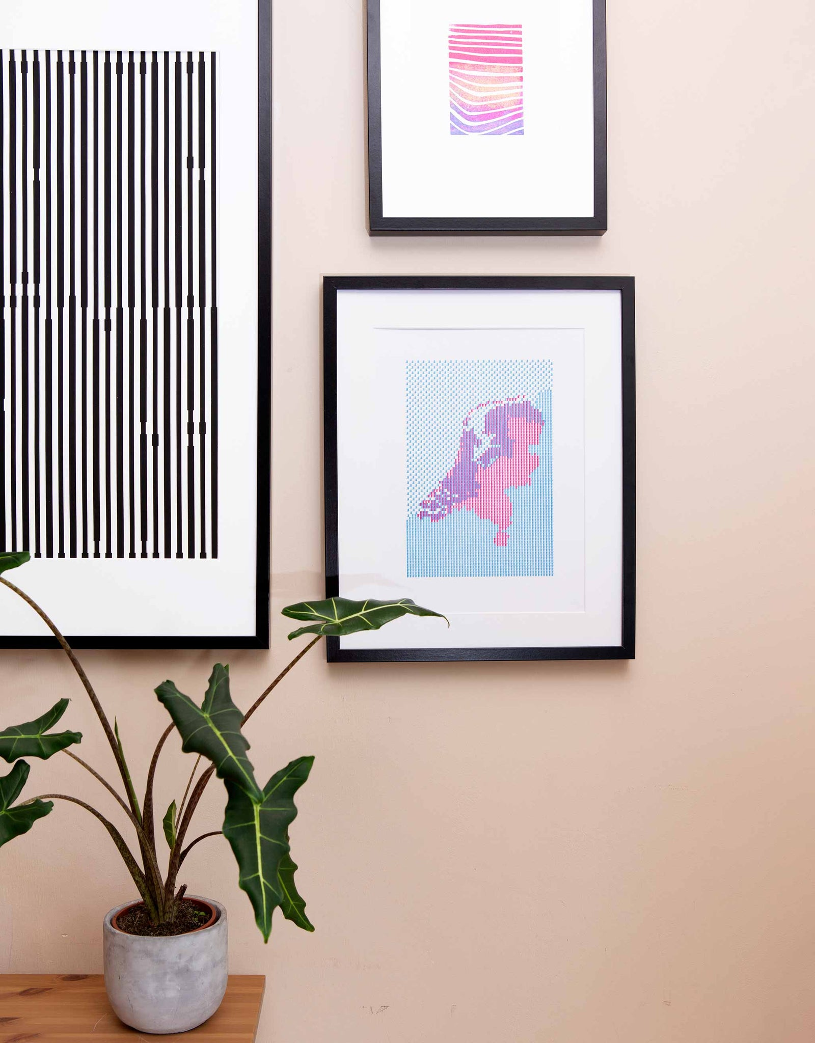 Letterpress patterned map of The Netherlands in magenta and blue. Shown in black frame on wall with plant and other art.
