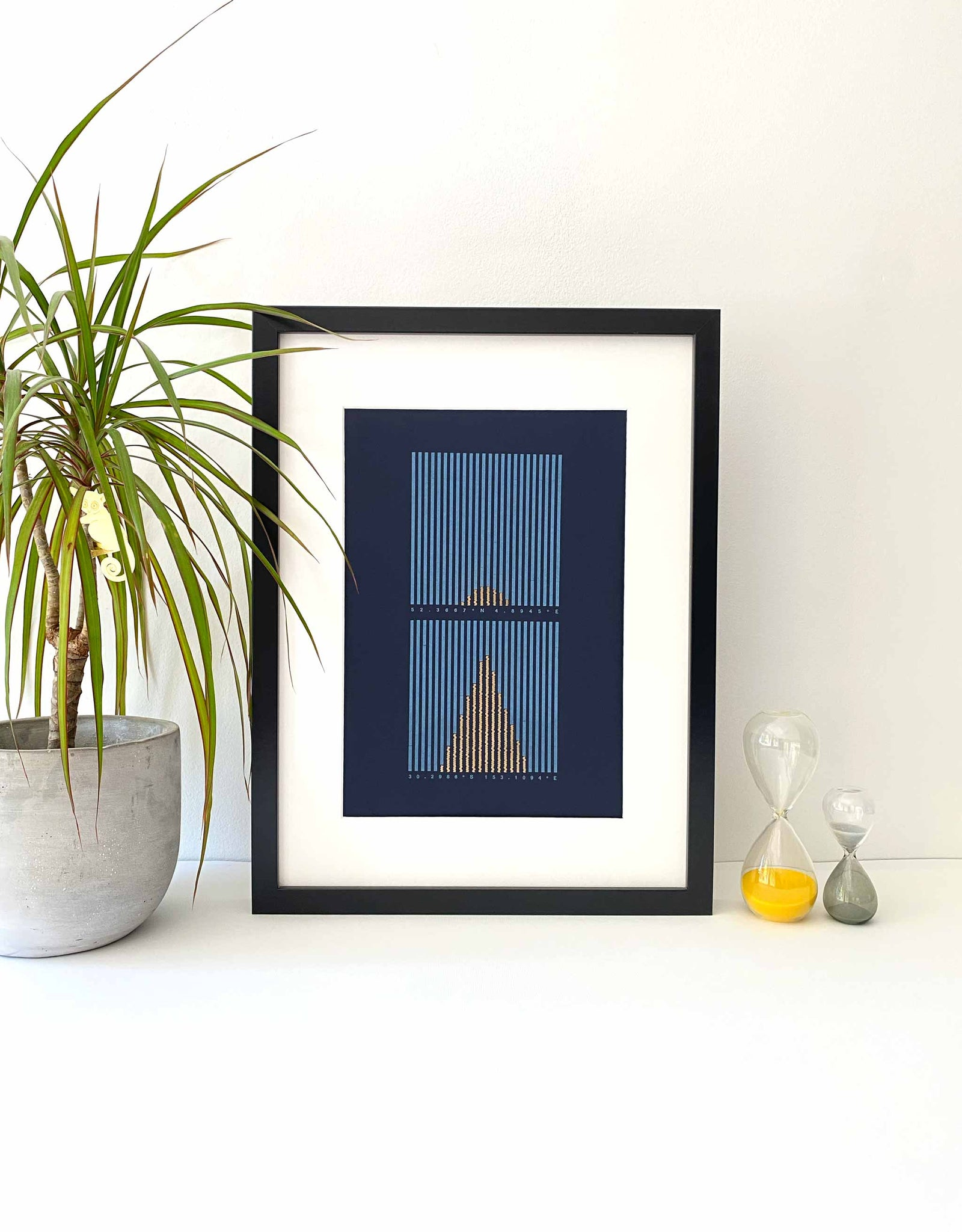 Framed Letterpress data print Sunlight Hours. Light blue and gold vertical lines on dark blue background. Lifestyle image with plant and props.