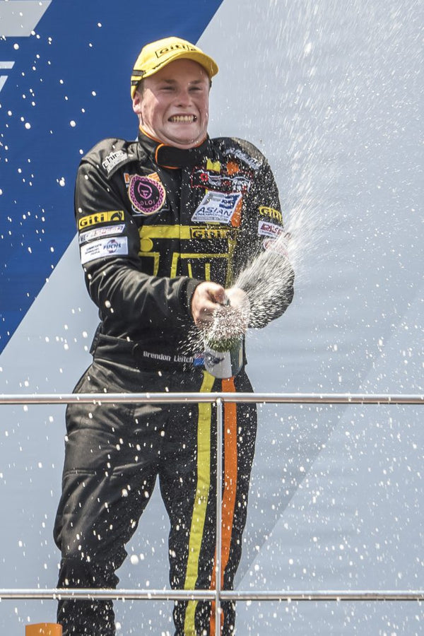 Driver Brendon Leitch sprays champagne from atop the winners' podium