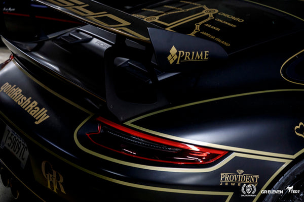 View of the rear of a Porsche with goldRush Rally logo