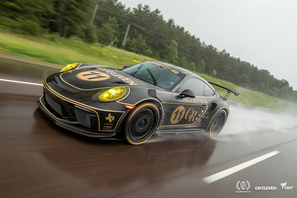 A black and gold Porche drives on a highway in wet conditions