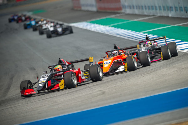 Three F3 cars compete for position during a turn