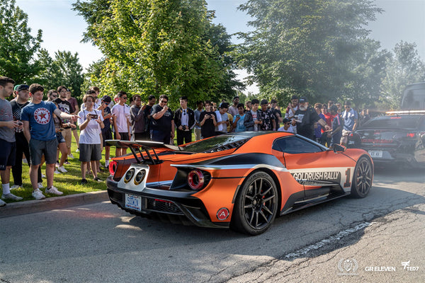 A crowd looks on at an orange supercar