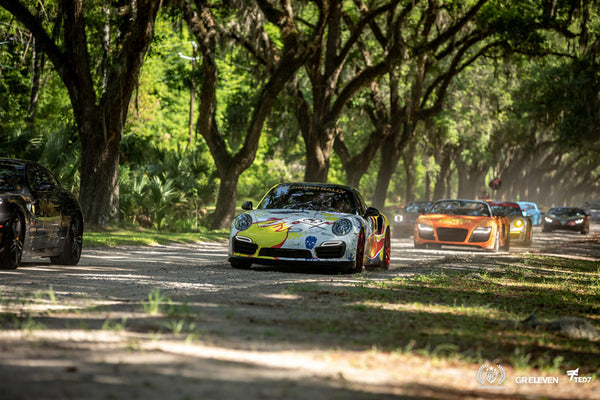 A group of cars participating in goldRush Rally drive under a canopy of trees