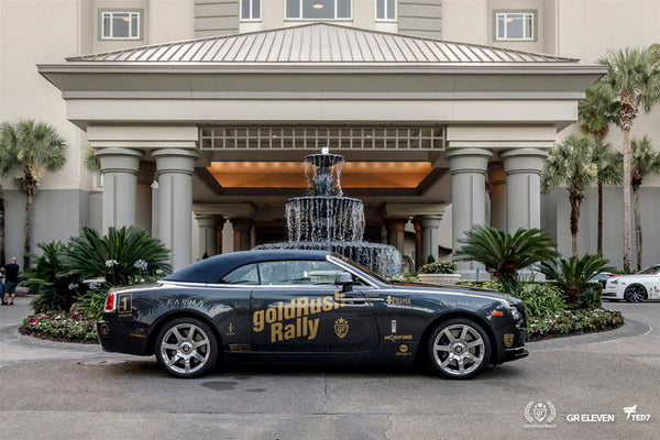 Car with goldRush Rally logo outside of a hotel