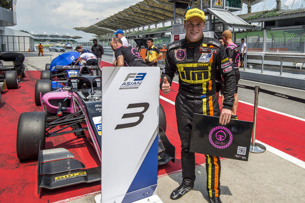 Oloi driver Brendon Leitch gives a thumbs up next to the pink Oloi F3 car