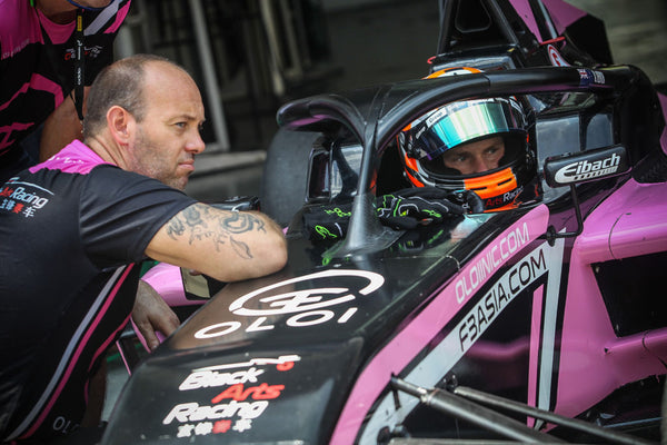 Driver Brendon Leitch speaks to BlackArts Racing team member from inside the cockpit of the pink Oloi F3 car