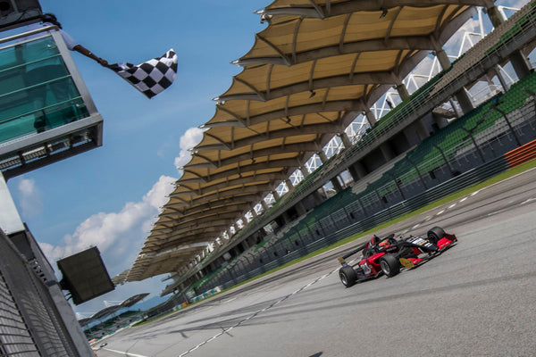 The checkered flag is waved from above as the red Oloi F3 car crosses the finish line