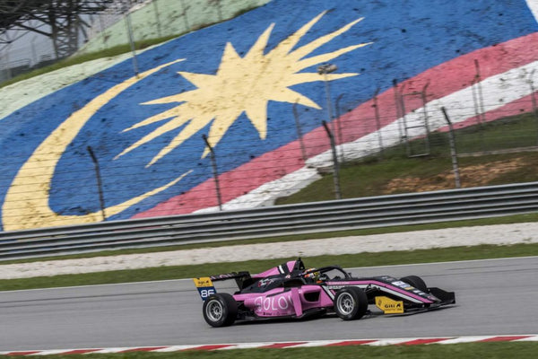 The Pink Oloi F3 car races on the track with the Malaysian flag painted in the grass in the background