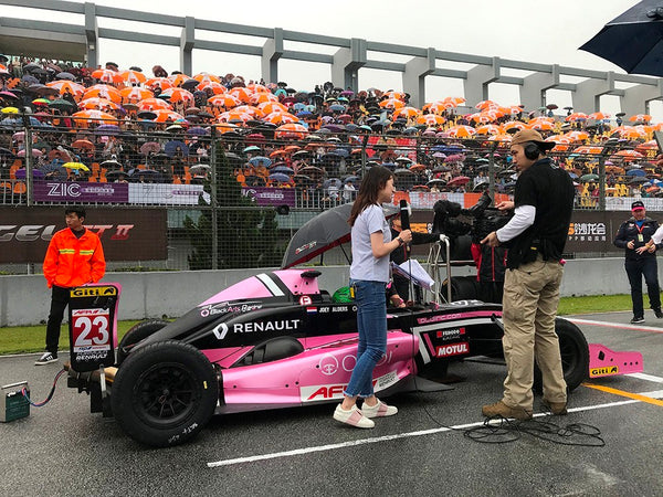 Asian Formula Renault media team members conduct an interview near the pink Oloi car on the starting grid