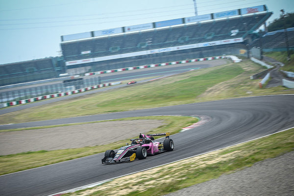 The pink Oloi F3 car navigates a turn on Suzuka International Circuit