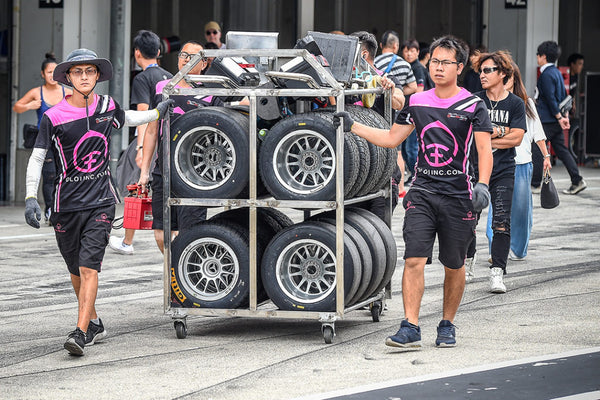 BlackArts Racing technicians wheel a rack of racing tires in the staging area at Suzuka International Circuit
