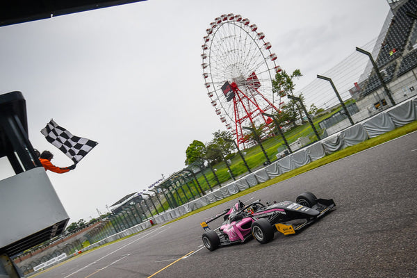 The checkered flag waves above the pink Oloi F3 car as it crosses the finish line
