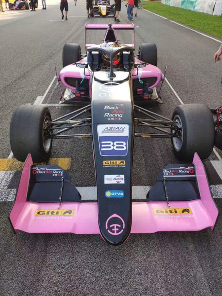 Head-on view of the pink Oloi F3 car and driver on the starting grid
