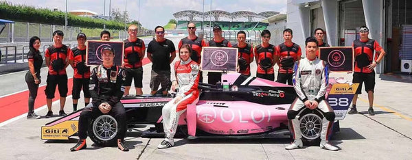 Drivers and crew of BlackArts Racing powered by Oloi pose with pink Oloi F3 car