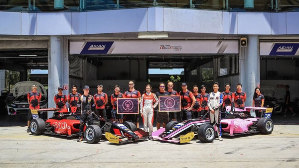 The drivers and crew of BlackArts Racing powered by Oloi pose with both the red and pink F3 cars