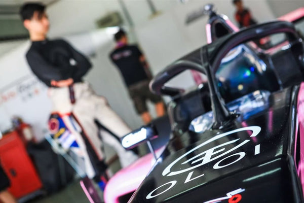 Closeup of pink Oloi F3 car with driver blurred in background