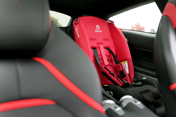 Child's car seat in the rear seat to match the black and red upholstery