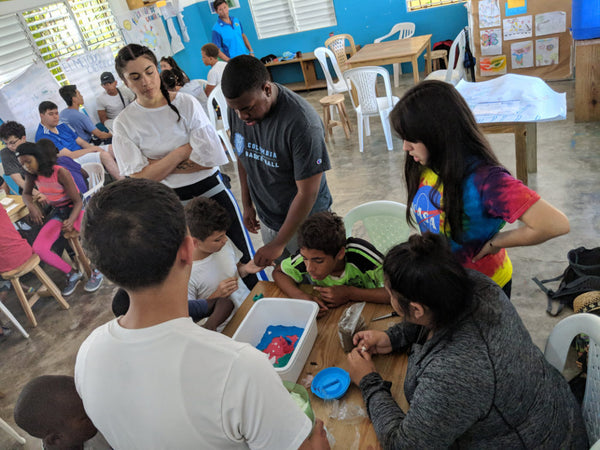 World Without Walls students guide children through a learning activity