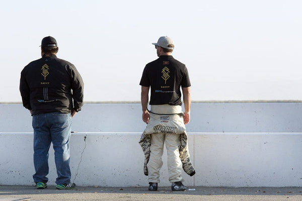 Techician and driver look on over the track at Buttonwillow Raceway