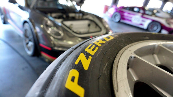 Stack of racing tires with Oloi's Porsche 911 Cup car in the background