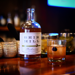 A glass of non-alcoholic whiskey in front of a bottle of Mashville