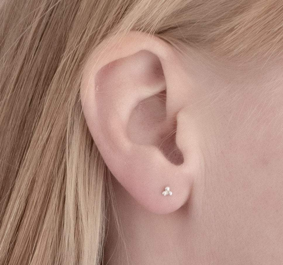 silver triple ball ear studs in ear