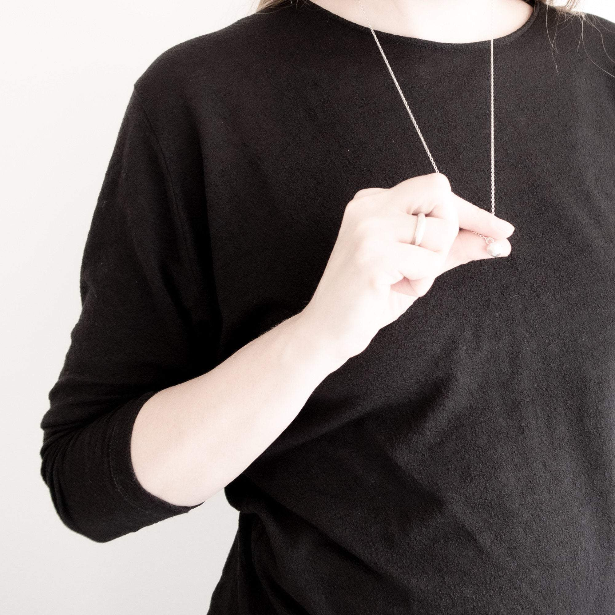model wearing facet pendant in silver