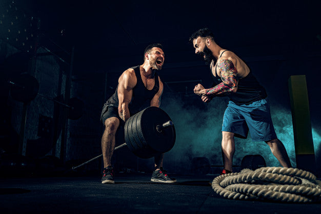 two muscular bearded people pushing weight
