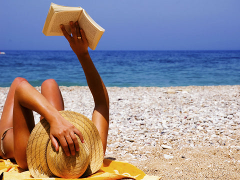 Girl in a bikini reading on the beach