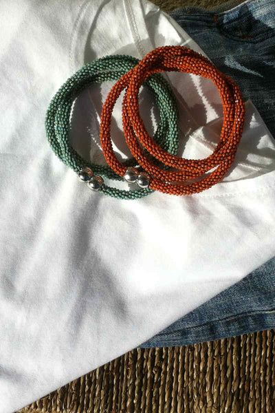 collection of orange and beaded wraparound bracelets