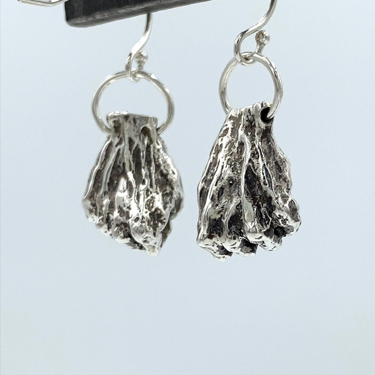 Resilience, Resistance, Power! I love to take elements from my work and make them into wearable art, each one hand made.  Hands in Fists  earrings. Sterling Silver - Holly Wilson