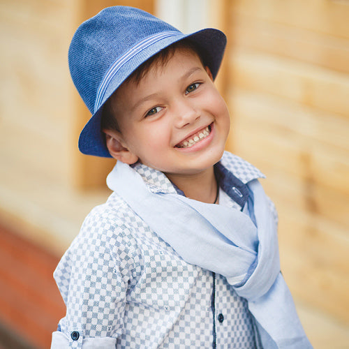 Young boy smiling, wearing a blue hat and spring clothing.