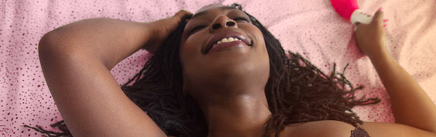 Woman with blissful smile lying back in bed