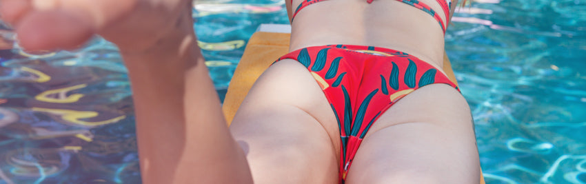 Closeup of woman's butt and legs who is lying on her stomach on a diving board, wearing a colorful bikini