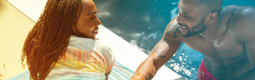 Couple gazes flirtatiously at each other at the edge of a swimming pool