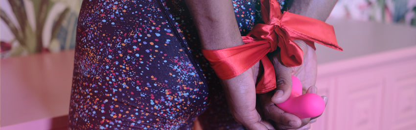 Closeup on a man's hand tied behind his back with a red ribbon, holding a Laya vibrator