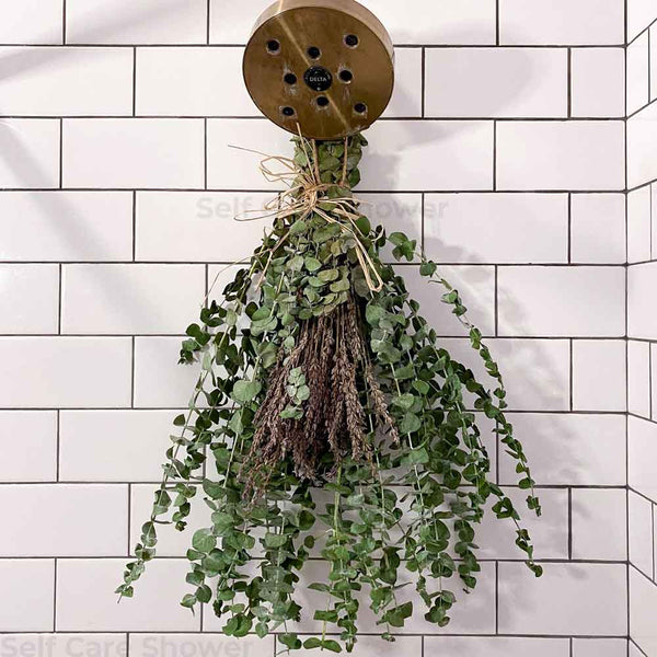 Eucalyptus hanging from shower head with fresh lavender and twine